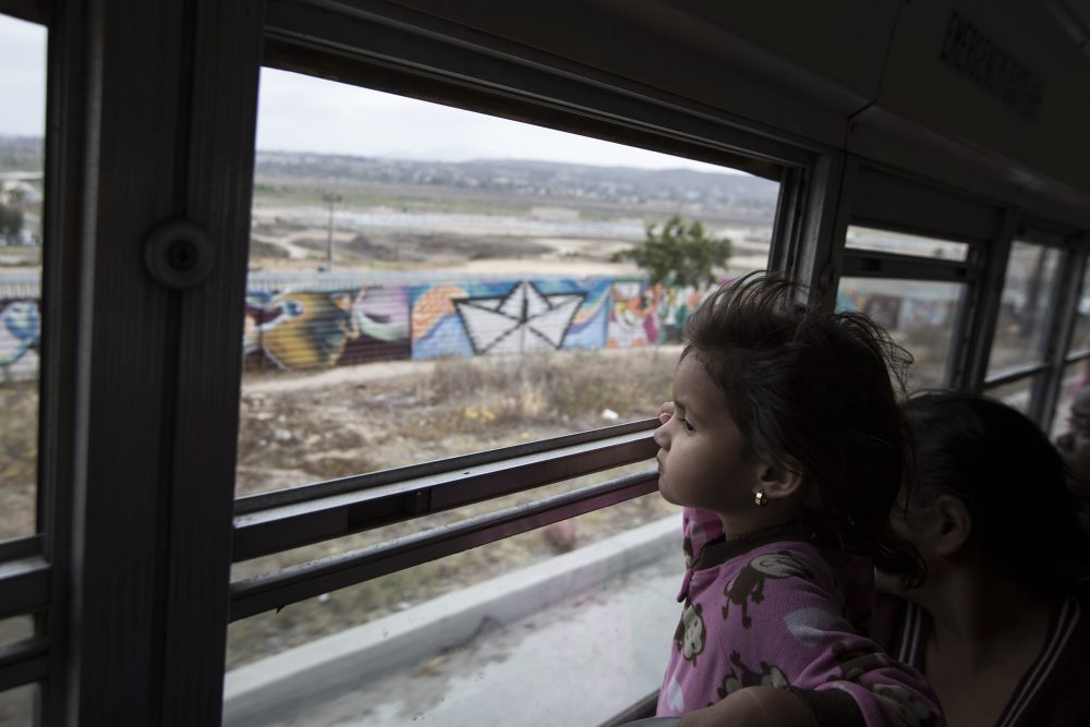 A Central American child who is traveling with a caravan of migrants, peers at the border wall from a bus carrying the group to a gathering of migrants living on both sides of the border, in Tijuana, Mexico, Sunday, April 29, 2018. U.S. immigration lawyers are telling Central Americans in a caravan of asylum-seekers that traveled through Mexico to the border with San Diego that they face possible separation from their children and detention for many months. They say they want to prepare them for the worst possible outcome. (Hans-Maximo Musielik/AP)