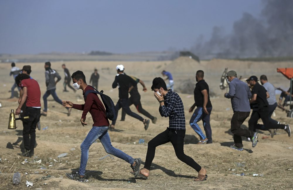 Palestinian protesters run for cover from teargas fired by Israeli troops during a protest at the Gaza Strip's border with Israel, Tuesday, May 15, 2018. Israel faced a growing backlash Tuesday and new charges of using excessive force, a day after Israeli troops firing from across a border fence killed dozens of Palestinians and wounded more than 2,700 at a mass protest in Gaza. (Khalil Hamra/AP)
