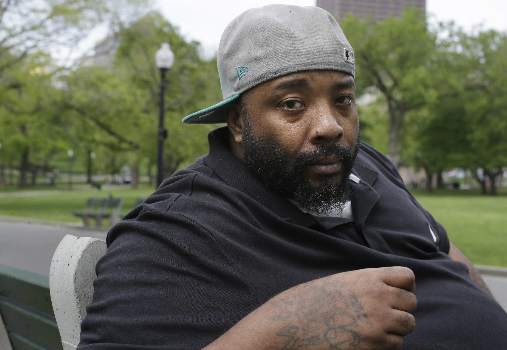 Emory Ellis sits for a photo in a park in Boston. Ellis was arrested in 2015 after he tried to buy breakfast at Burger King using a $10 bill that the cashier thought was fake. (Steven Senne/AP)