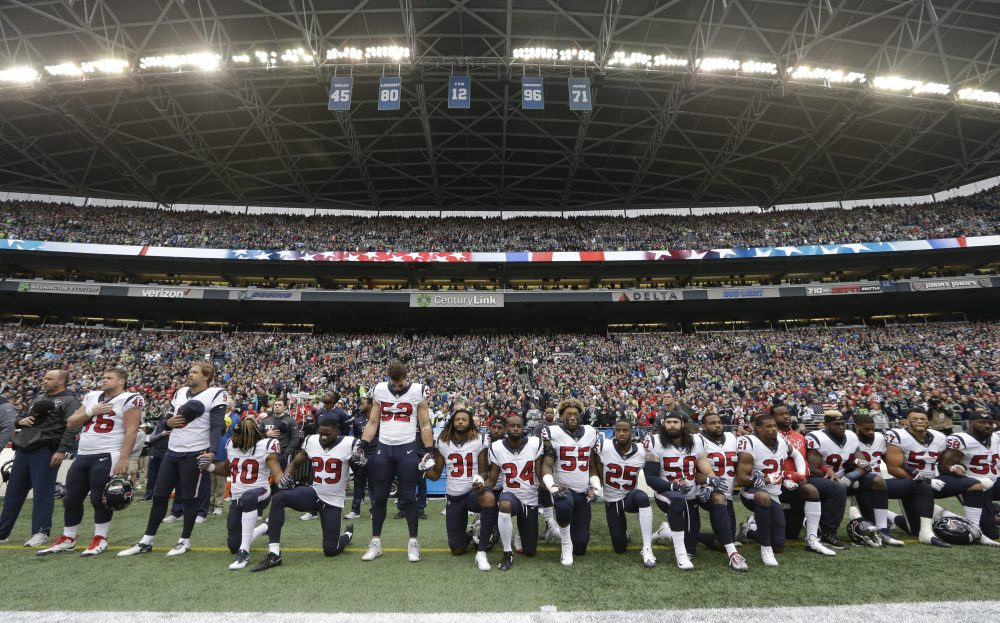 "In this Oct. 29, 2017, file photo, Houston Texans players kneel and stand during the singing of the national anthem before an NFL football game against the Seattle Seahawks, in Seattle. NFL owners have approved a new policy aimed at addressing the firestorm over national anthem protests, permitting players to stay in the locker room during the ""The Star-Spangled Banner"" but requiring them to stand if they come to the field. The decision was announced Wednesday, May 23, 2018, by NFL Commissioner Roger Goodell during the league's spring meeting in Atlanta. (Elaine Thompson/AP)"