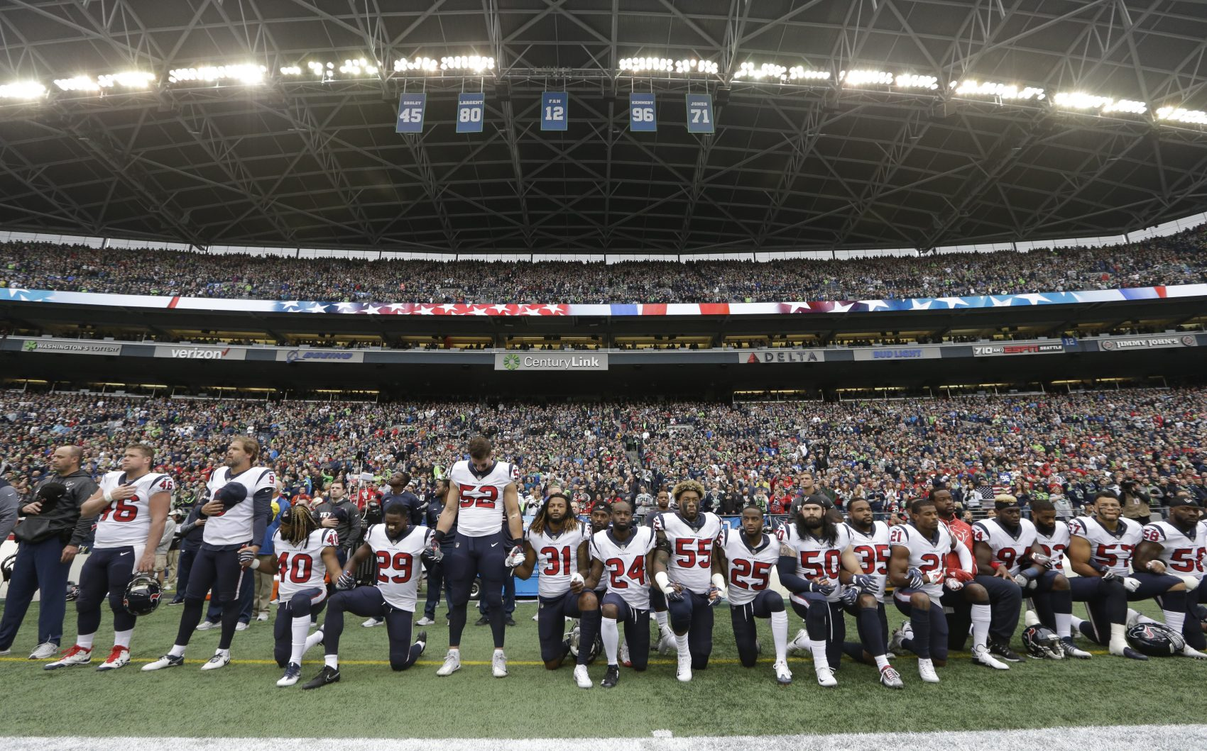 """In this Oct. 29, 2017, file photo, Houston Texans players kneel and stand during the singing of the national anthem before an NFL football game against the Seattle Seahawks, in Seattle. NFL owners have approved a new policy aimed at addressing the firestorm over national anthem protests, permitting players to stay in the locker room during the """"The Star-Spangled Banner"""" but requiring them to stand if they come to the field. The decision was announced Wednesday, May 23, 2018, by NFL Commissioner Roger Goodell during the league's spring meeting in Atlanta. (Elaine Thompson/AP)"""