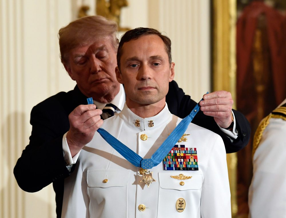 "President Trump awards the Medal of Honor to Master Chief Special Warfare Operator Britt K. Slabinski during a ceremony in the White House Thursday. Slabinski oversaw a daring 2002 assault and rescue mission on a snowy Afghanistan mountaintop and carried a ""seriously wounded teammate down a sheer cliff face"" while leading ""an arduous trek across one kilometer of precipitous terrain, through waist-deep snow while continuing to call fire on the enemy."" (Susan Walsh/AP)"