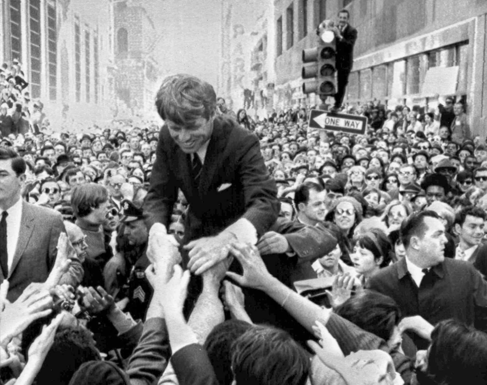 In this April 2, 1968 file photo U.S. Sen. Robert F. Kennedy, D-NY, shakes hands with people in a crowd while campaigning for the Democratic party's presidential nomination on a street corner, in Philadelphia. (Warren Winterbottom/AP)