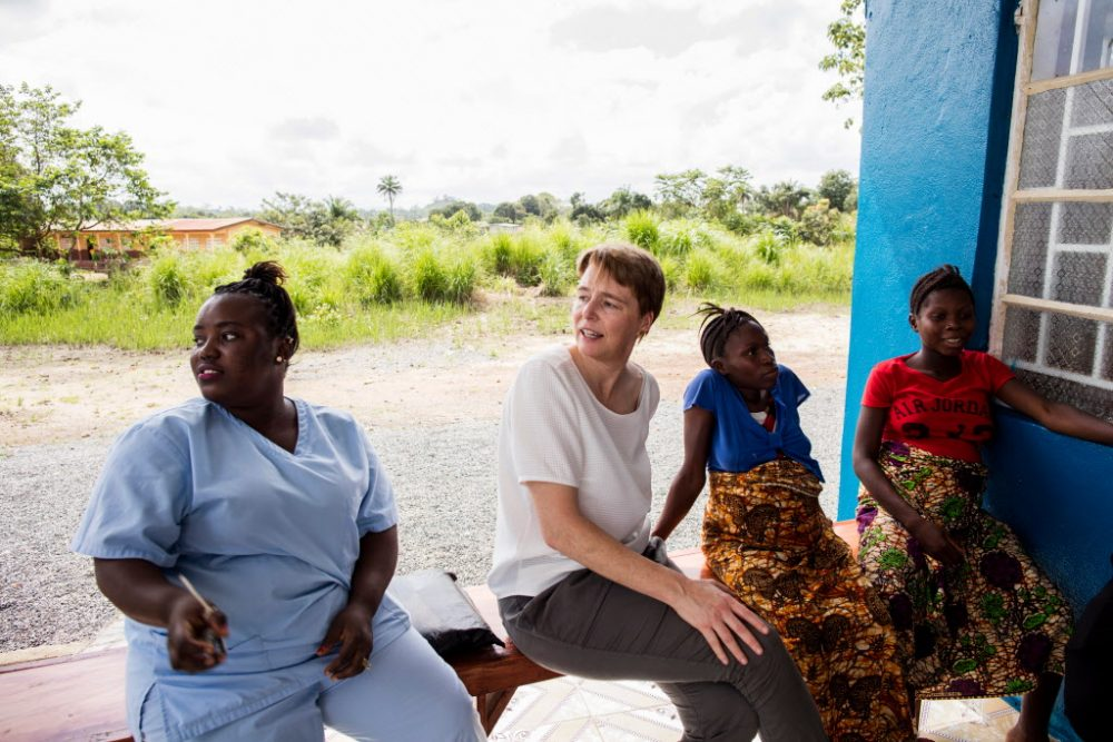 The author, Ophelia Dahl (center), and nurse Ndamba Mansaray (left) visit with Isah Kaimoko (second from right) and Kumba Finohtwo, two pregnant women staying at the Wellbody Birth Waiting Home in Kono, Sierra Leone, on Oct. 24, 2017. (Jon Lascher/Partners In Health)