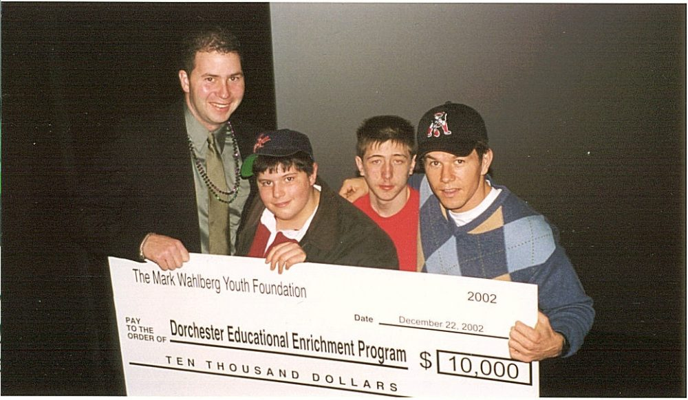 Mark Wahlberg, right, presents a check to Project DEEP, a Dorchester nonprofit, around 2002. From left, Project DEEP's John Hanlon, and brothers Tim and Joey Langis of Dorchester. (Courtesy)