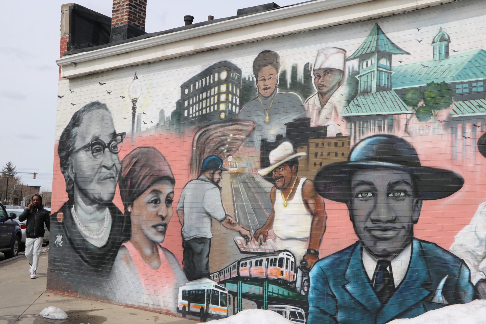 "A depiction of Melnea Cass, far left, and other neighborhood icons, in the ""Faces of Dudley"" mural on Washington Street. (Rachel Paiste/WBUR)"