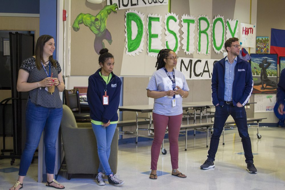 "In front of a ""Destroy MCAS"" sign on the wall, from left, Megan Sanchez, Samantha Suarez, Pertreena Cherrie and Peter Perry-Friedman pause for a morning staff meeting at KIPP Academy Boston. (Carrie Jung/WBUR)"