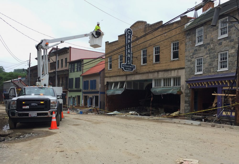Utility workers check the power lines on Main Street after Sunday's floodwaters that raged down the downtown district in Ellicott City, Md., Tuesday, May 29, 2018. (Courtney Columbus/AP)