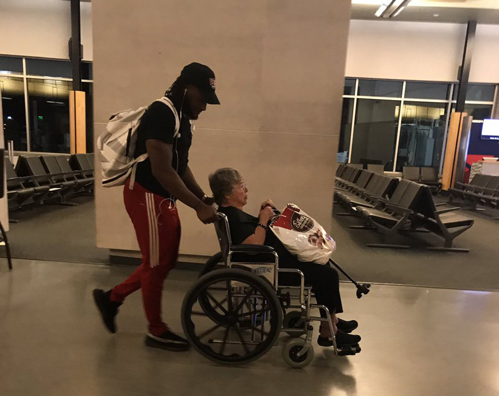 Green Bay Packers running back Aaron Jones wheels an airline passenger through Appleton International Airport after the airline failed to provide that service for her. (Courtesy Monica Allen via Twitter)