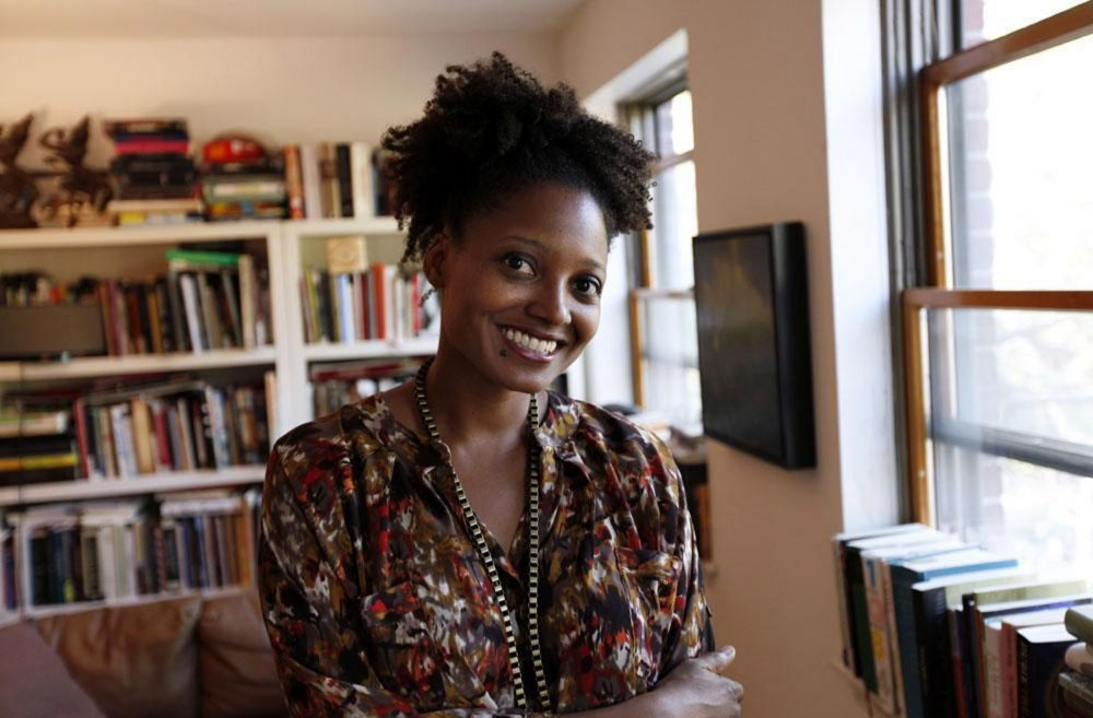 "Tracy K. Smith poses in her Brooklyn apartment after winning the Pulitzer Prize for poetry her poetry collection ""Life on Mars,"" in April, 2012 in New York. (AP/Jason DeCrow)"
