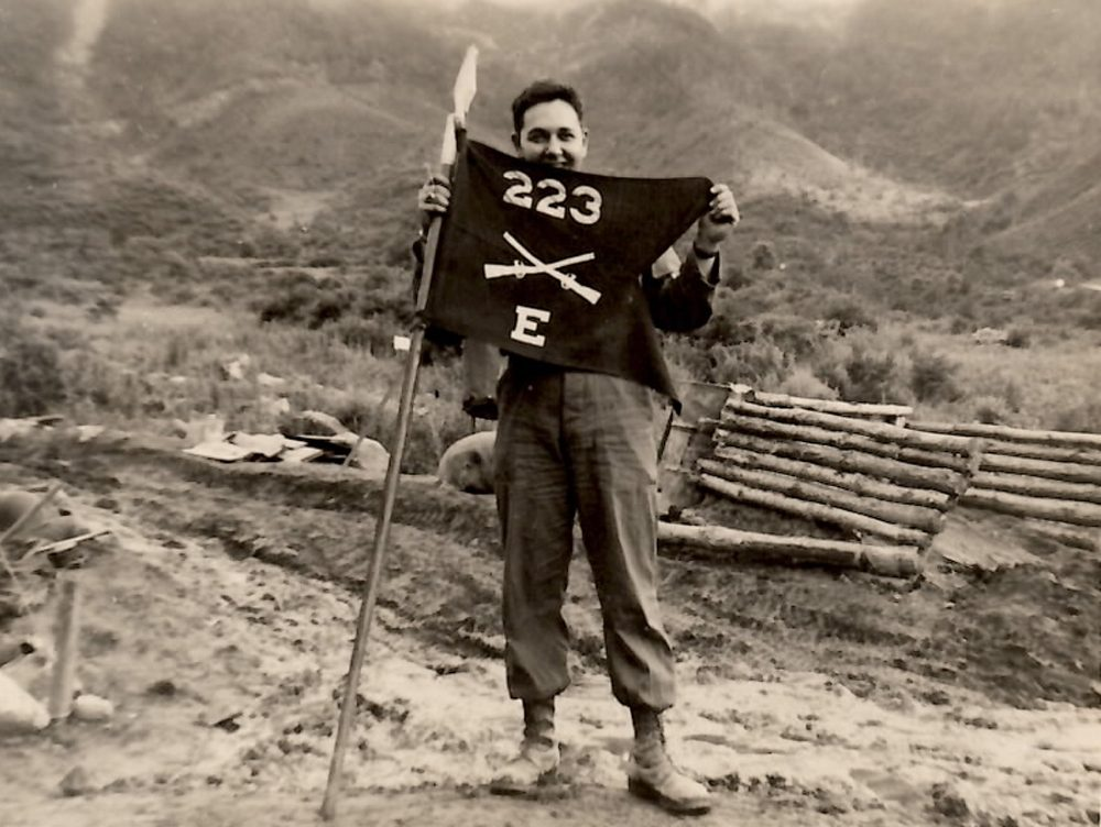 John Cort poses with his company's flag at the so-called Punchbowl, in Korea. (Courtesy John Cort)