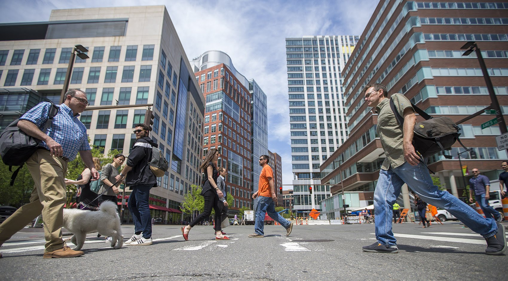 People crossing at the intersection of Ames and Main Streets. Kendall Square is home to many biotech and high tech companies including the Broad Institute, left and Google, right. (Jesse Costa/WBUR)