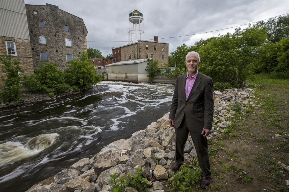 Mayor of Smiths Falls Shawn Pankow stands by the Rideau Canal where the old water treatment facility, left, will be converted into a hotel and hospitality center proposed by the Canopy Growth Corporation. (Jesse Costa/WBUR)