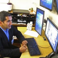 In this Sept. 2016 photo, critical care doctor Shadi Battah in Anchorage, Alaska, converses with clinicians at the Iliuliuk Family and Health Services on Unalaska Island during a demonstration of a new telemedicine partnership with Providence Alaska Medical Center. (Rachel D'Oro/AP)