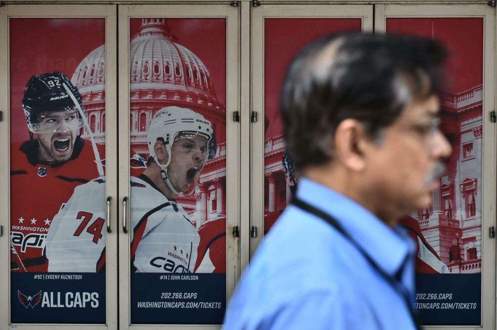 A pedestrian passes by a poster outside of the Capital One Arena on June 5 1215ab275