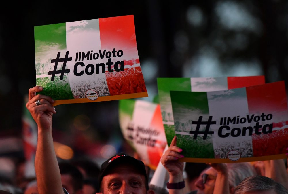 "M5S supporters hold banners reading ""My vote counts"" during a meeting to celebrate Italy's new government in Rome, on June 2, 2018. (Alberto Pizzoli/AFP/Getty Images)"