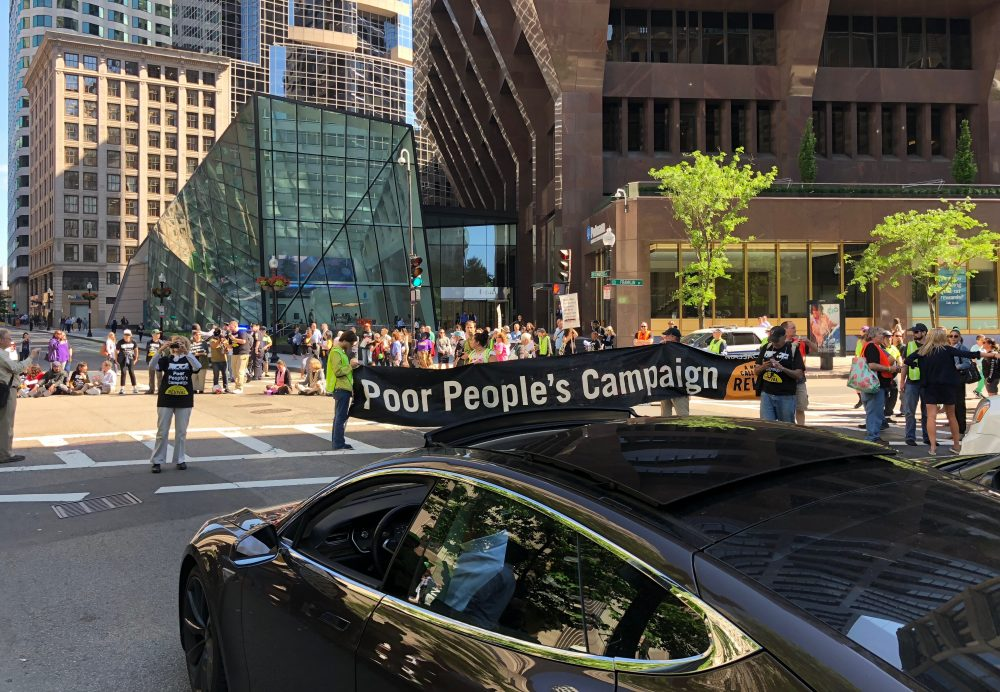 Activists with the Poor People's Campaign shut down the intersection of Congress and Franklin Streets Monday afternoon in downtown Boston. (Andy Metzger/State House News Service)