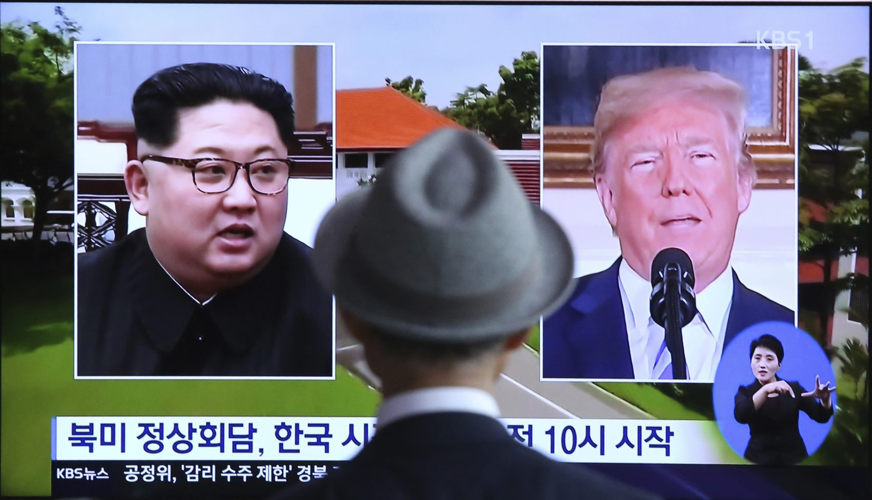 """A man watches a TV screen showing file footage of U.S. President Donald Trump, right, and North Korean leader Kim Jong Un during a news program at the Seoul Railway Station in Seoul, South Korea, Monday, June 11, 2018.  Final preparations are underway in Singapore for Tuesday's historic summit between President Trump and North Korean leader Kim, including a plan for the leaders to kick things off by meeting with only their translators present, a U.S. official said. The signs read: """"Summit between the United States and North Korea."""" (Ahn Young-joon/AP)"""