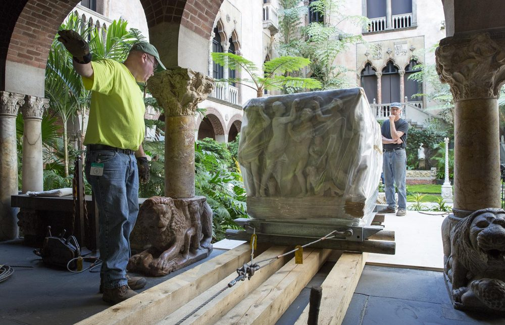 The rigging crew rolls the sarcophagus wrapped in plastic along planks through the museum. (Robin Lubbock/WBUR)