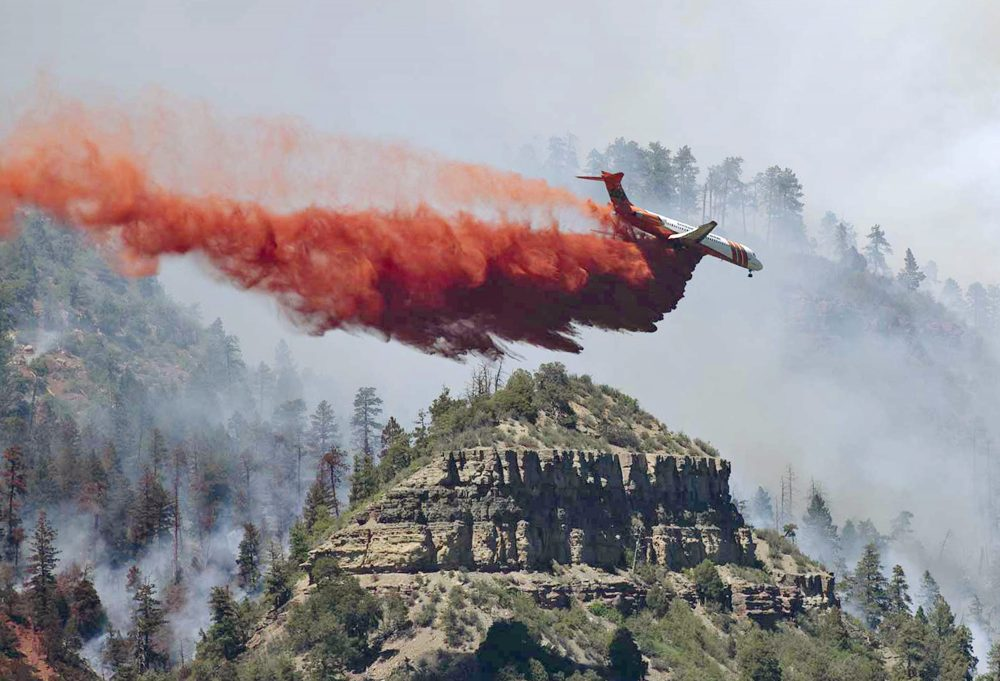 In this photo provided by Jerry Day, an aircraft makes a fire retardant drop on a wildfire in the mountains and forests near Durango, Colo., Friday, June 8, 2018. (Jerry Day via AP)