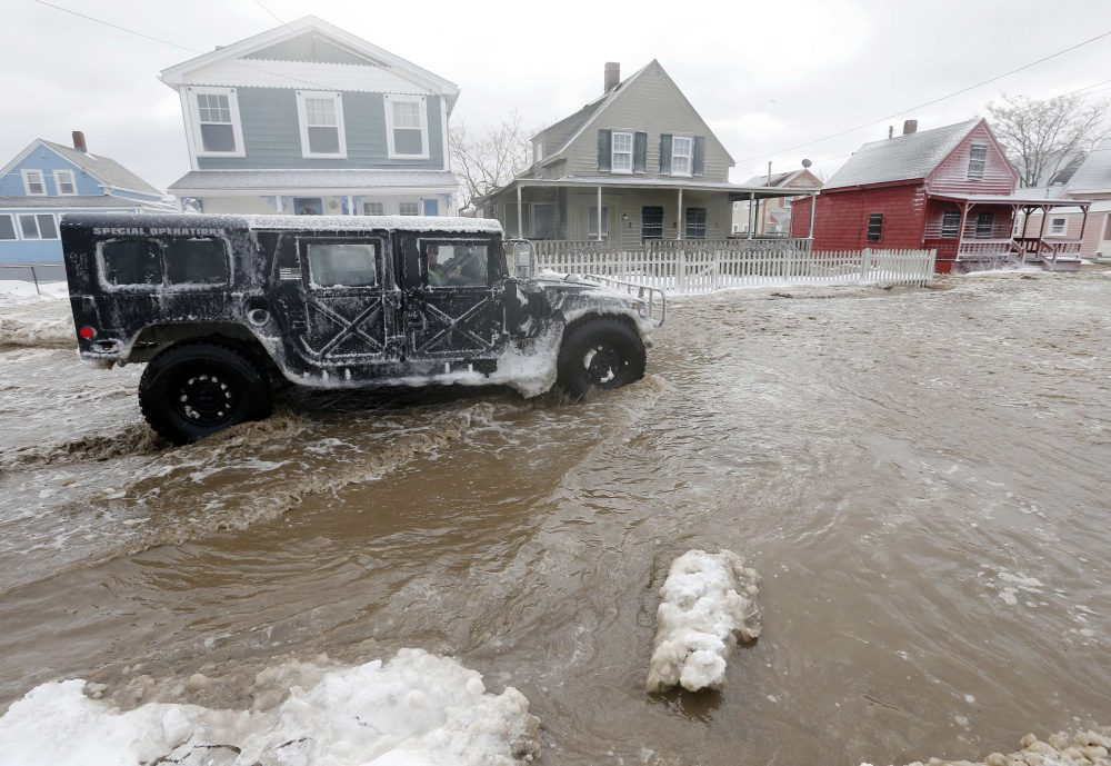A police special operations vehicle drives down a flooded street along the shore in Hull, Mass., Friday, Jan. 3, 2014, in the wake of a winter storm.  (Michael Dwyer/AP)
