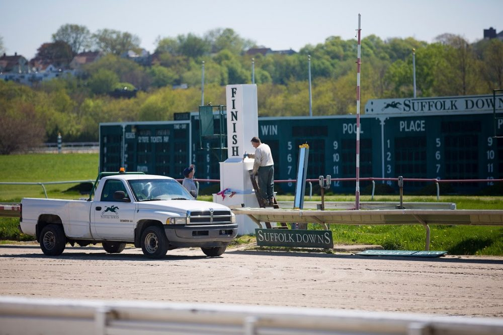 Suffolk Downs workers repaint the post at the finish line. The racetrack site is now the largest redevelopment project in the region. (Jesse Costa/WBUR)