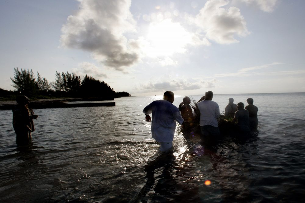 A group of men wade into the ocean as they push a small raft loaded with offerings to their ancestors out to sea Sunday, June 19, 2005 as part a Juneteenth celebration. (Wilfredo Lee/AP)