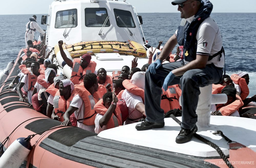 "This June 12, 2018 photo released Wednesday, June 13, 2018 by French NGO ""SOS Mediterranee"" shows migrants waving after being transferred from the Aquarius ship to Italian Coast Guard boats, in the Mediterranean Sea. Italy dispatched two ships Tuesday to help take 629 migrants stuck off its shores on the days-long voyage to Spain in what is forecast to be bad weather, after the new populist government refused them safe port in a dramatic bid to force Europe to share the burden of unrelenting arrivals. (Kenny Karpov/SOS Mediterranee via AP)"