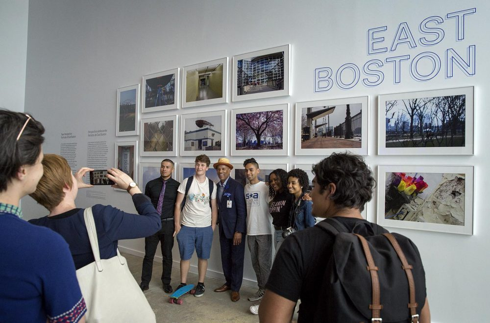 Visitors to the inaugural exhibition of the ICA Watershed pose for a photo in front of a wall of photographs of East Boston by teens from the ICA's digital photography program. (Robin Lubbock/WBUR)