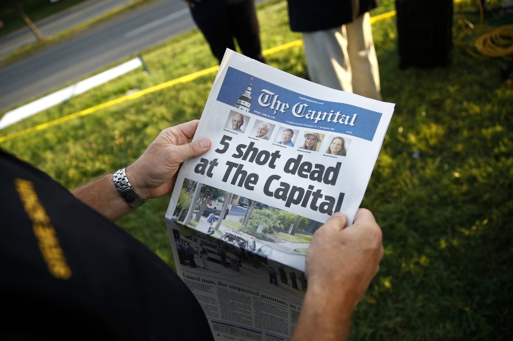 Steve Schuh, county executive of Anne Arundel County, holds a copy of The Capital Gazette near the scene of a shooting at the newspaper's office, Friday, June 29, 2018, in Annapolis, Md. A man armed with smoke grenades and a shotgun attacked journalists in the building Thursday, killing several people before police quickly stormed the building and arrested him, police and witnesses said. (Patrick Semansky/AP)