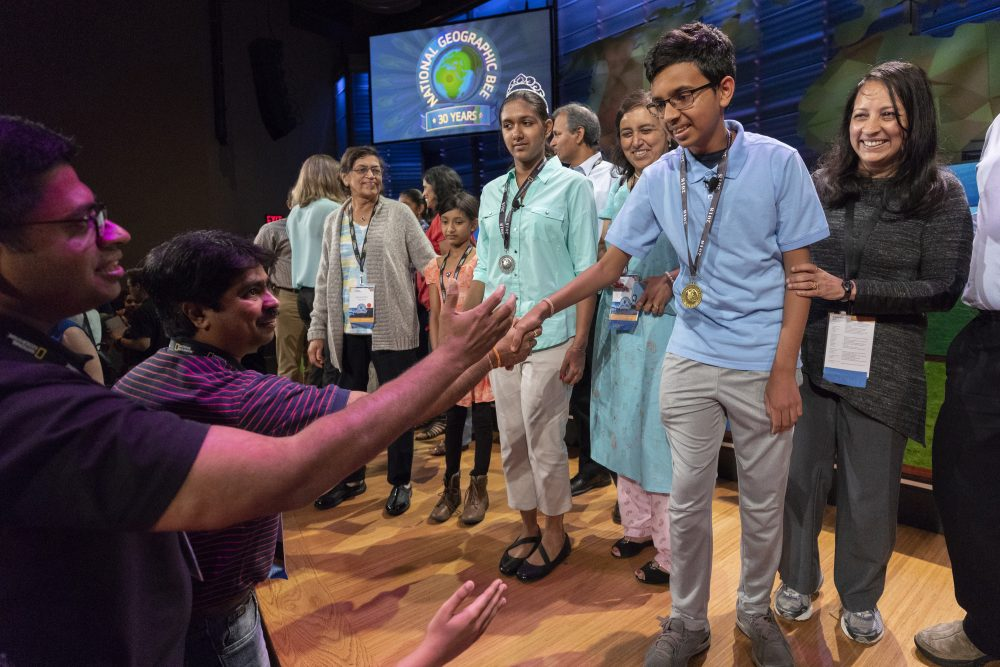 2018 National Geographic Bee Champion Venkat Ranjan of California shakes hands with audience members after the final competition in Washington, D.C., on May 23. Also pictured on stage is second-place finisher Anoushka Buddhikot of New Jersey. (Mark Thiessen/National Geographic)