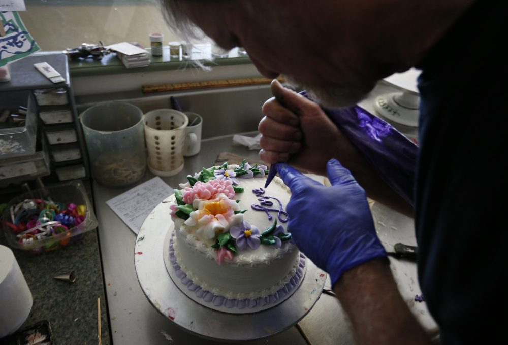In this March 10, 2014 photo, Masterpiece Cakeshop owner Jack Phillips decorates a cake inside his store, in Lakewood, Colo. (Brennan Linsley/AP)