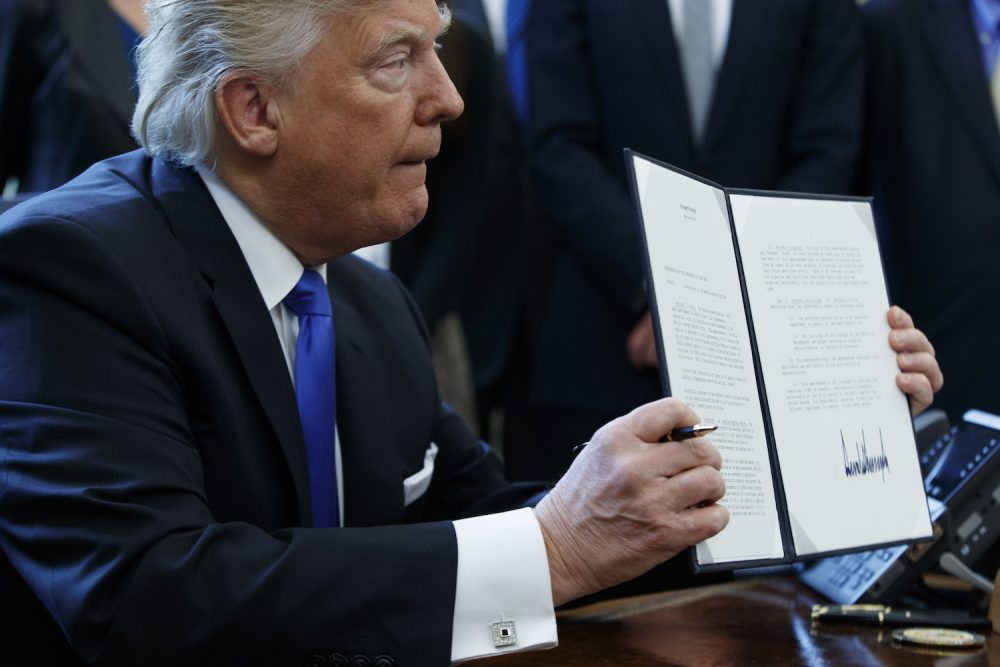 President Donald Trump shows off his signature on an executive order about the Dakota Access pipeline, Tuesday, Jan. 24, 2017, in the Oval Office of the White House in Washington. (Evan Vucci/AP)
