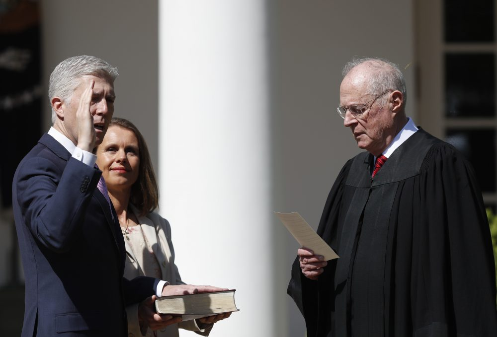 Supreme Court Justice Anthony Kennedy administers the judicial oath to Justice Neil Gorsuch during a re-enactment in the Rose Garden of the White House on April 10, 2017. Holding the bible is Gorsuch's wife Marie Louise Gorsuch. (Carolyn Kaster/AP)