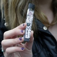 In this April 11 photo, an unidentified 15-year-old high school student displays a vaping device near her school's campus in Cambridge. (Steven Senne/AP)