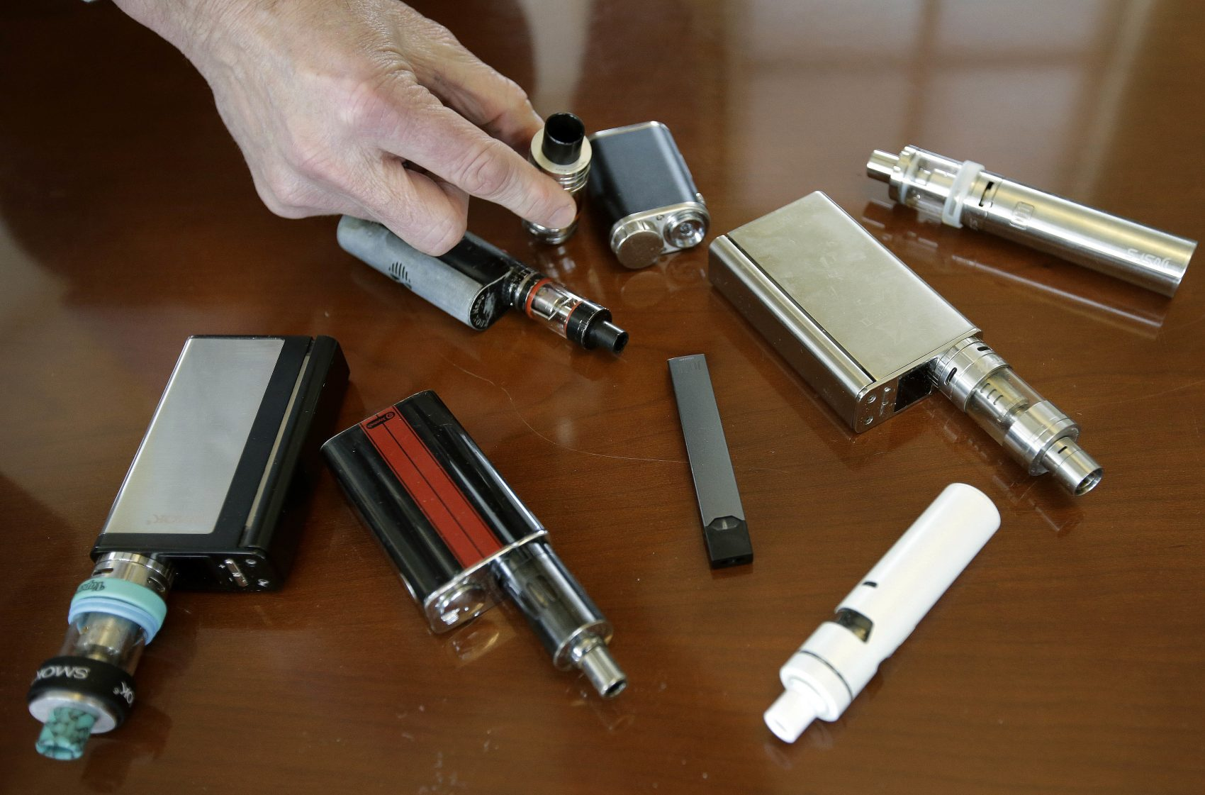 Marshfield High School principal Robert Keuther displays vaping devices that were confiscated from students in such places as restrooms or hallways at the school. (Steven Senne/AP)