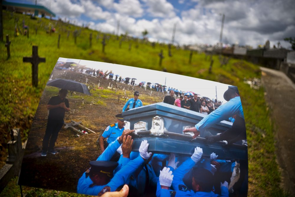 A printed photo taken on Sept. 29, 2017 showing police lifting the coffin of officer Luis Angel Gonzalez Lorenzo, who was killed during the passage of Hurricane Maria when he tried to cross a river in his car, is shown at the same cemetery in Aguada, Puerto Rico, May 31, 2018. The local police force of Aguadilla and Aguada lacks about a dozen officers since the storm, due to resignations and retirements. The U.S. territory's bankruptcy has frozen promotions, salaries, new hires and some police academies have even closed. (Ramon Espinosa/AP)