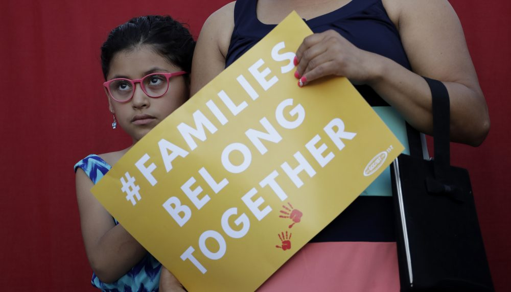 """A girl stands with her mother during a Rally For Our Children event to protest a new """"zero-tolerance"""" immigration policy that has led to the separation of families, Thursday, May 31, 2018, in San Antonio. (Eric Gay/AP)"""