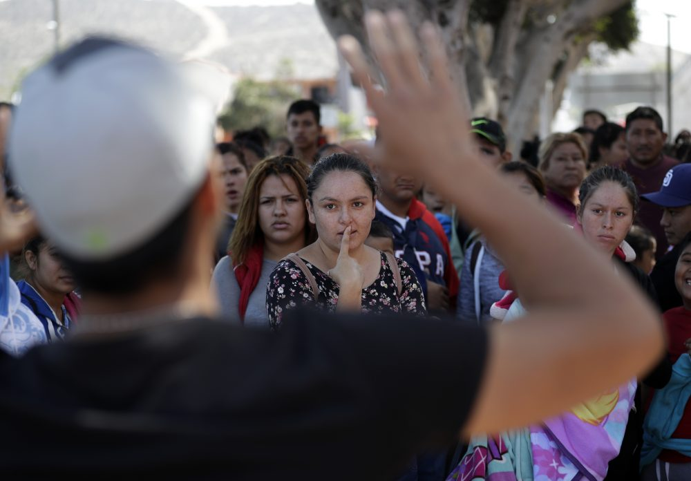 In this June 13, 2018 photo, an organizer speaks to families as they wait to request political asylum in the United States, across the border in Tijuana, Mexico. In Tijuana, Latin Americans fleeing drug violence in their countries are camped out and waiting to apply for U.S. asylum - undeterred by the new directive from Attorney General Jeff Sessions this week to bar victims of gang violence from qualifying. (Gregory Bull/AP)