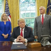 President Donald Trump, center, with Homeland Security Secretary Kirstjen Nielsen, left, and Vice President Mike Pence, right, before signing an executive order to end family separations, during an event in the Oval Office of the White House in Washington, Wednesday, June 20, 2018. (Pablo Martinez Monsivais/AP)