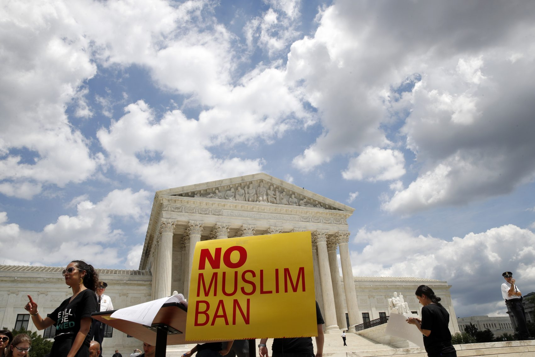 People protest Tuesday against the Supreme Court ruling upholding President Trump's travel ban. (Jacquelyn Martin/AP)