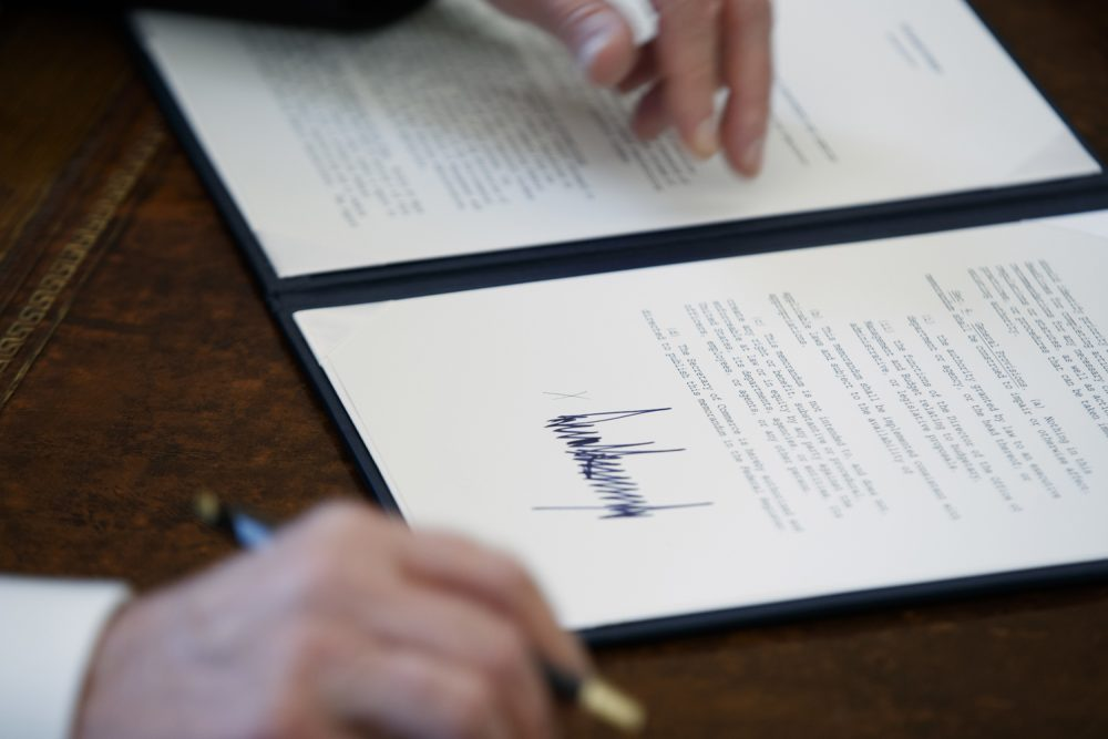 In this Jan. 24, 2017, file photo, the signature of President Donald Trump is seen on an executive order in Oval Office of the White House in Washington. Trump has taken 18 executive actions since being sworn into office on Jan. 20. Some of the papers he signed were executive orders that dealt with building the wall he promised along the U.S.-Mexico border; temporarily banning entry to the U.S. by refugees and people from seven majority-Muslim nations; and beginning to chip away at the Affordable Care Act. (AP Photo/Evan Vucci, File)