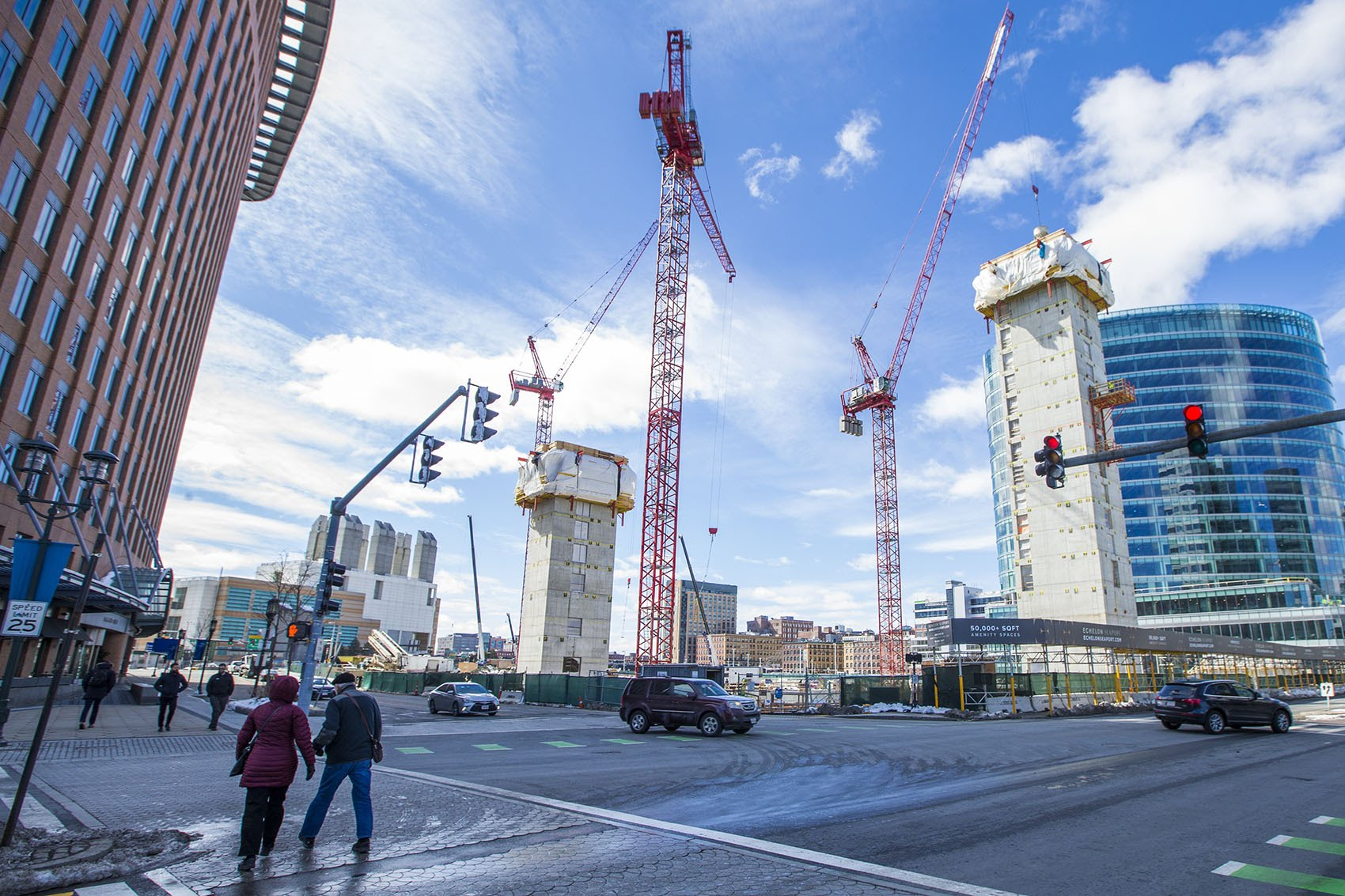 Cranes stretch into the sky in March over what will become three buildings of luxury apartments and condos. (Jesse Costa/WBUR)