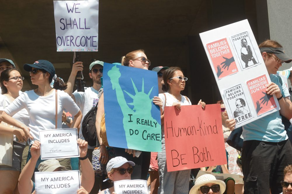 Protesters hold signs at an immigration rally in Boston in 2018. (Quincy Walters/WBUR)
