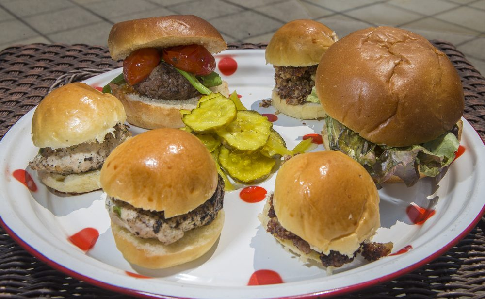 A plate of assorted burgers. (Clockwise from top left) the Classic burger, the Superiority burger, and the Turkey-feta burger. (Jesse Costa/WBUR)