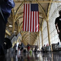 Travelers walk to their gates in the concourse of Reagan National Airport in advance of the Fourth of July holiday on June 29, 2018, in Washington, D.C. TSA has projected that 28.3 million passengers may be expected on the travel dates of June 28 through July 9. (Win McNamee/Getty Images)