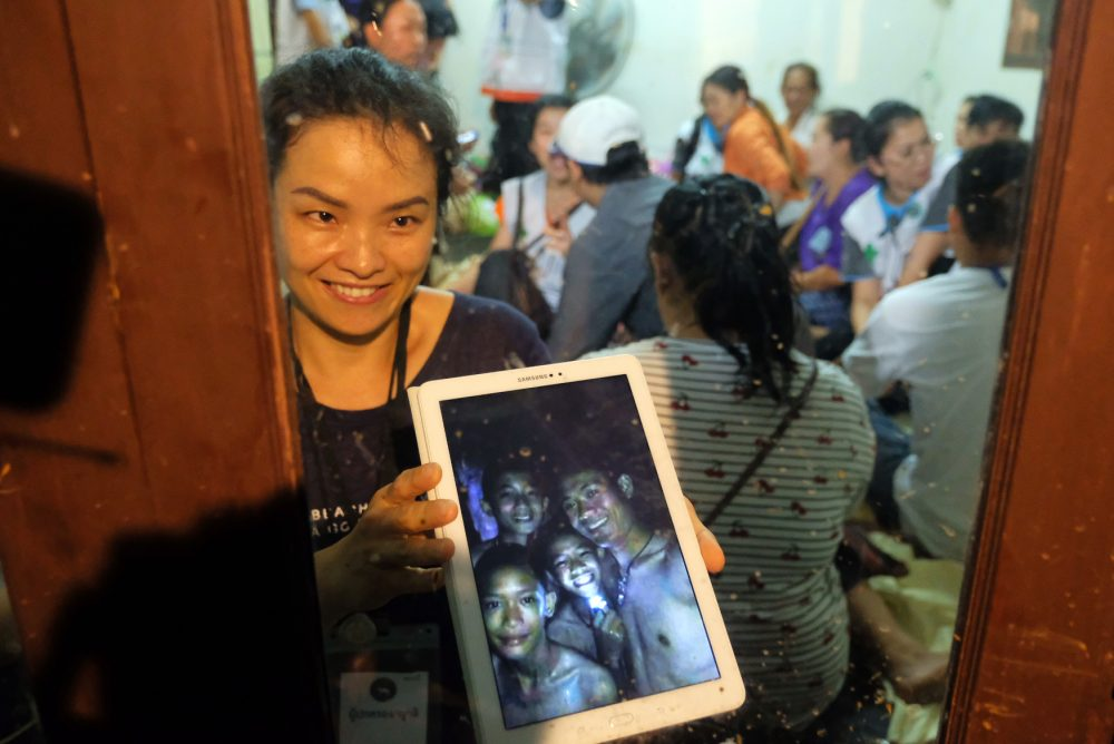 Relatives of the missing boys show photos of them after the 12 boys and their soccer coach were found alive in the cave where they've been missing for over a week after monsoon rains blocked the main entrance on July 2, 2018 in Chiang Rai, Thailand. (Linh Pham/Getty Images)