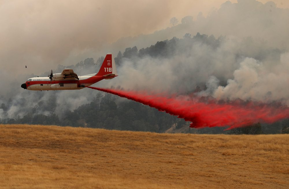 A firefighting air tanker drops fire retardant on a hillside ahead of the County fire on July 2, 2018 in Esparto, Calif. (Justin Sullivan/Getty Images)