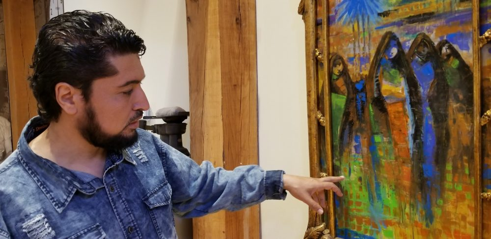 Iraqi Ahmed Alkarkhi points out the colors he began painting with since moving to the U.S. (Carmel Delshad/WAMU)
