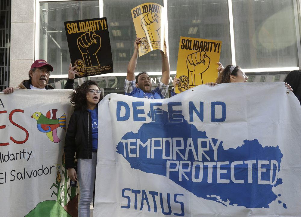 Supporters of temporary protected status immigrants hold signs and cheer before a March, 2018 news conference in San Francisco announcing a lawsuit against the Trump administration over its decision to end TPS. (Jeff Chiu/AP)